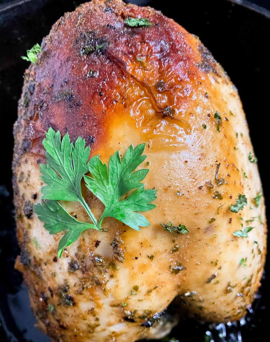 A cast iron Dutch oven holding a freshly baked Cajun roast turkey breast.