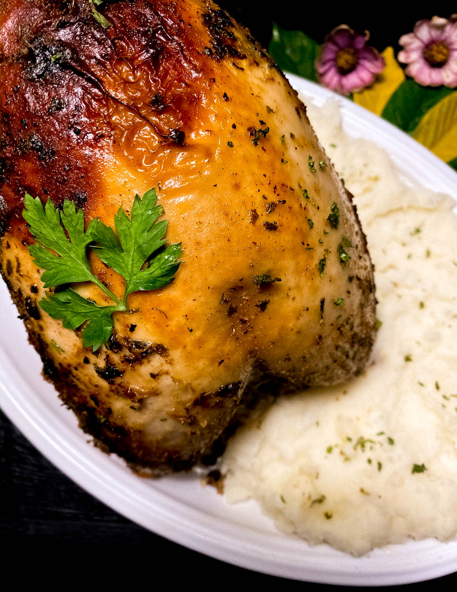 An oval white plate filled with Cajun roast turkey breast and mashed potatoes.