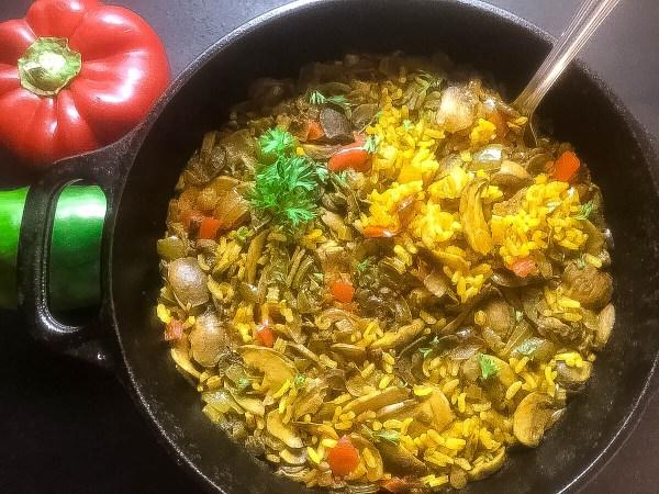 Cajun Trinity Turmeric Rice With Mushrooms cooked in small cast iron Dutch oven. | https://asprinklingofcayenne.com