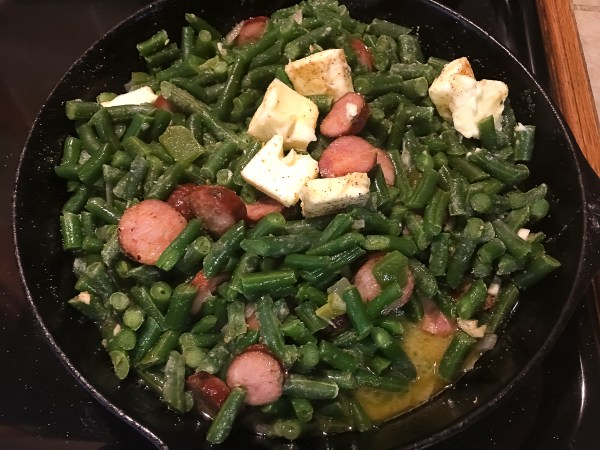 Cajun smothered green beans with sausage cooking down in a cast iron skillet.
