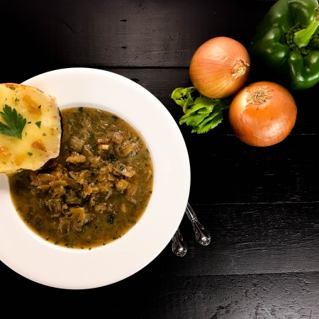A bowl of Gluten Free Cajun French Onion Chicken Soup from A Sprinkling of Cayenne food blog. | https://asprinklingofcayenne.com