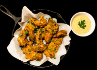 A cast iron skillet filled with fried then baked grain free chicken tenders and wings with dipping sauce against a black background.