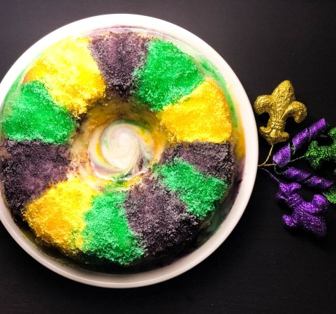 A plate holding a Blueberry Cream Cheese Gluten Free King Cake Bundt Cake.