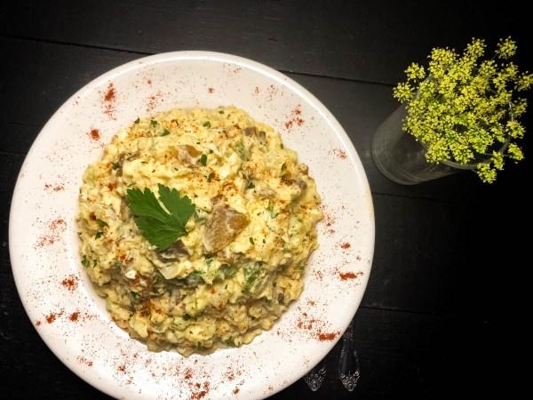 Plate of Best Ever Cajun Potato Salad with flowers. | https://asprinklingofcayenne.com