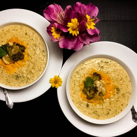 Two bowls filled with broccoli cauliflower cheese soup with magenta and yellow flowers on a black background.