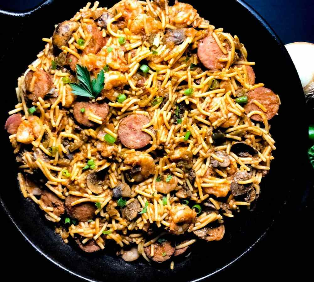 A black skillet with sausage and shrimp jambalaya pasta garnished with garden parsley leaves.