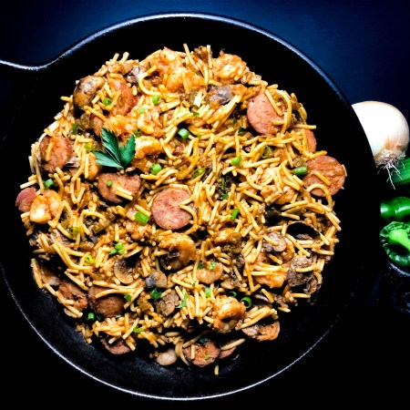 A cast iron skillet filled with freshly prepared shrimp and sausage jambalaya pasta.