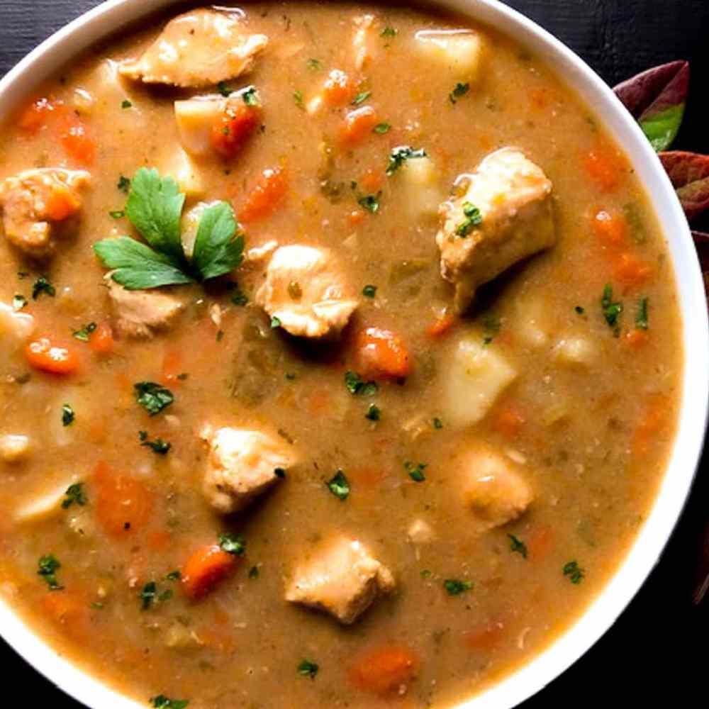 A big round, white bowl of Grain Free Cajun Chicken Stew. | https://asprinklingofcayenne.com