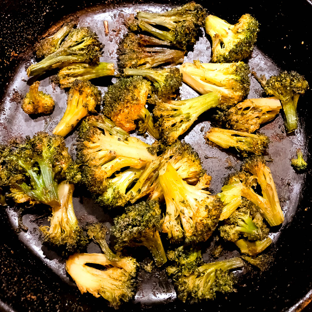 Roasted broccoli in a cast iron skillet. | https://asprinklingofcayenne.com