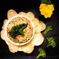 Grain Free Cheesy Roasted Broccoli Dip with a potato chip flower around the bowl. | https:/asprinklingofcayenne.com