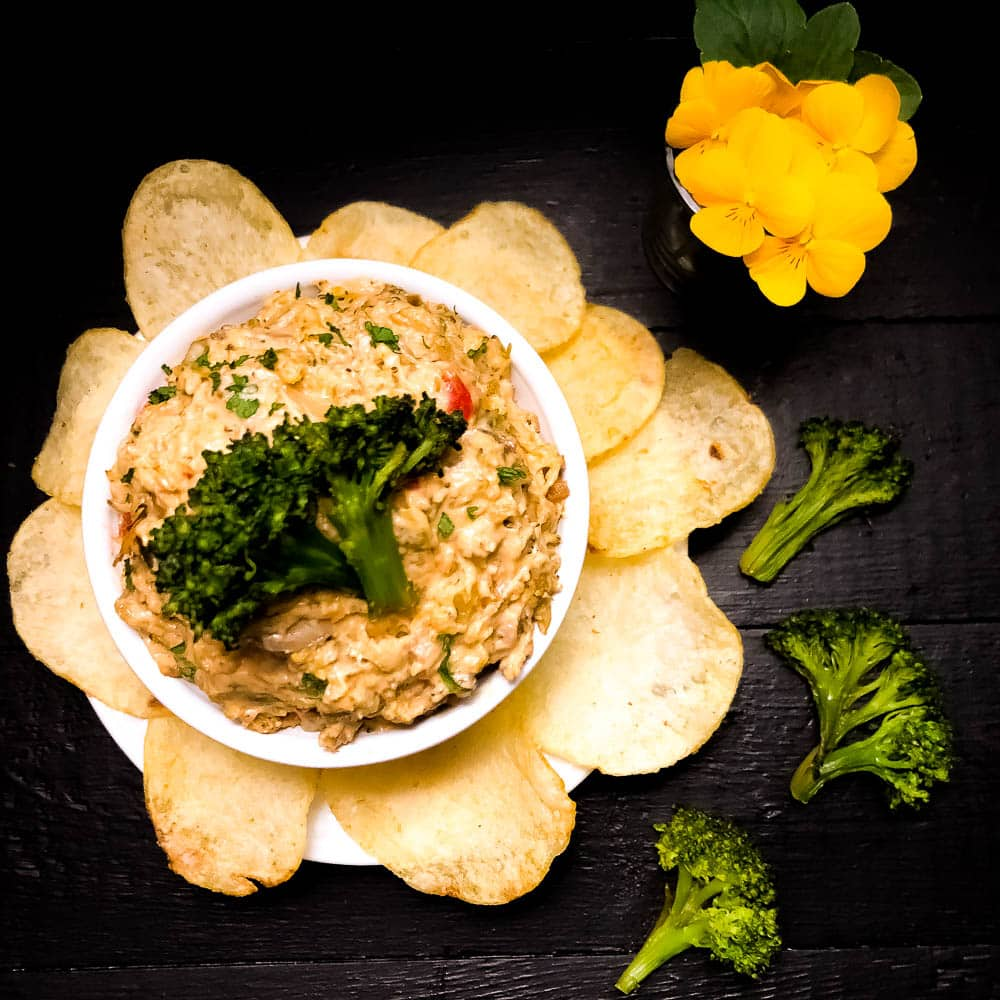 Grain Free Cheesy Roasted Broccoli Dip with a potato chip flower around the bowl. | https:/asprinklingofcayenne.com