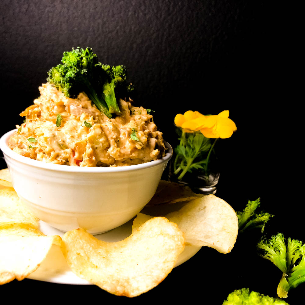 A side view of Grain Free Cheesy Roasted Broccoli Dip in a white bowl against a black background. | https://asprinklingofcayenne.com