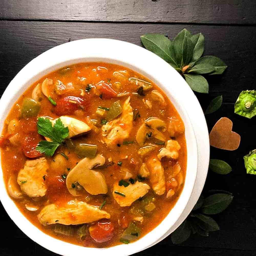 A white round bowl filled with Grain or Gluten Free Cajun Chicken Sauce Piquante. | https://asprinklingofcayenne.com