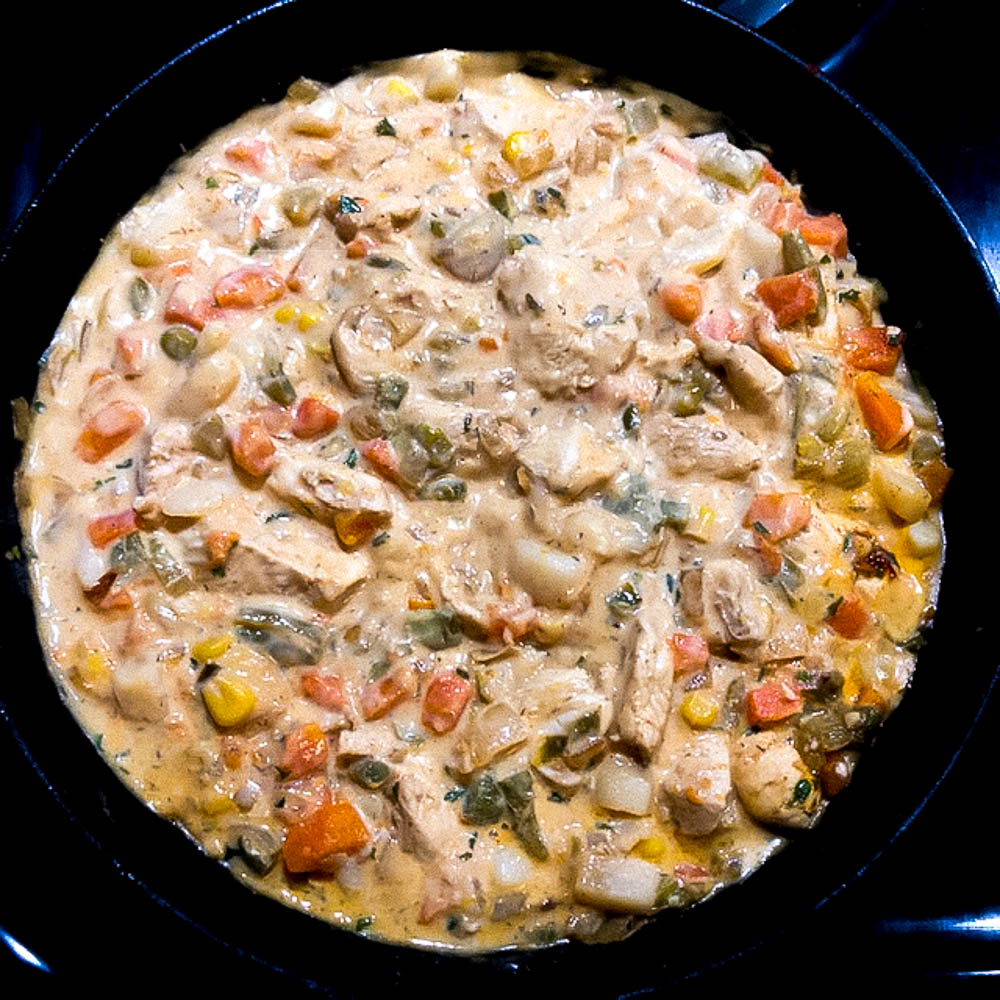 The Cajun trinity, chicken, milk, chicken broth, veggies and seasonings cooking down in a cast iron skillet.