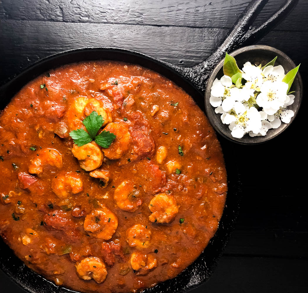 A cast iron skillet filled with south Louisiana shrimp Creole with a vase of white flowers. | https://asprinklingofcayenne.com