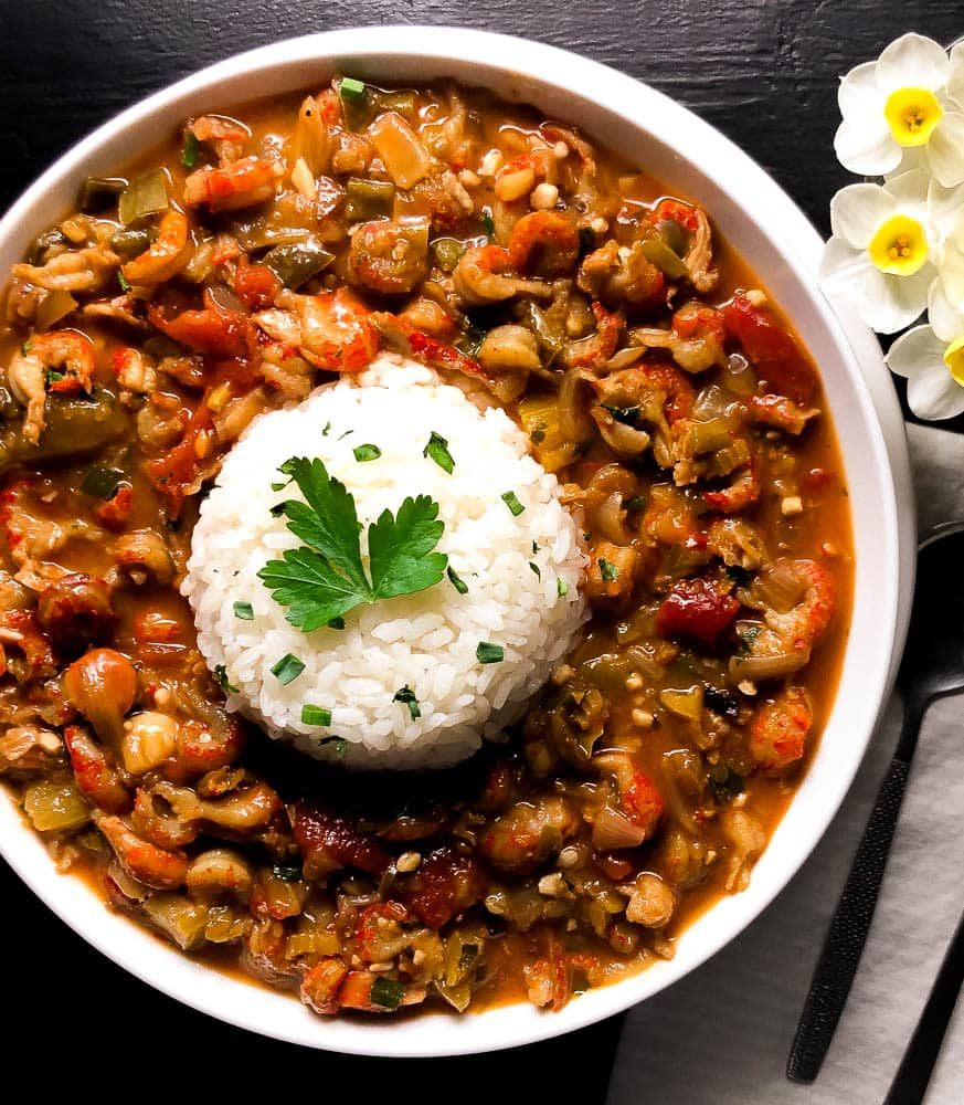 A round white bowl filled with Cajun Crawfish Etouffee. | https://asprinklingofcayenne.com