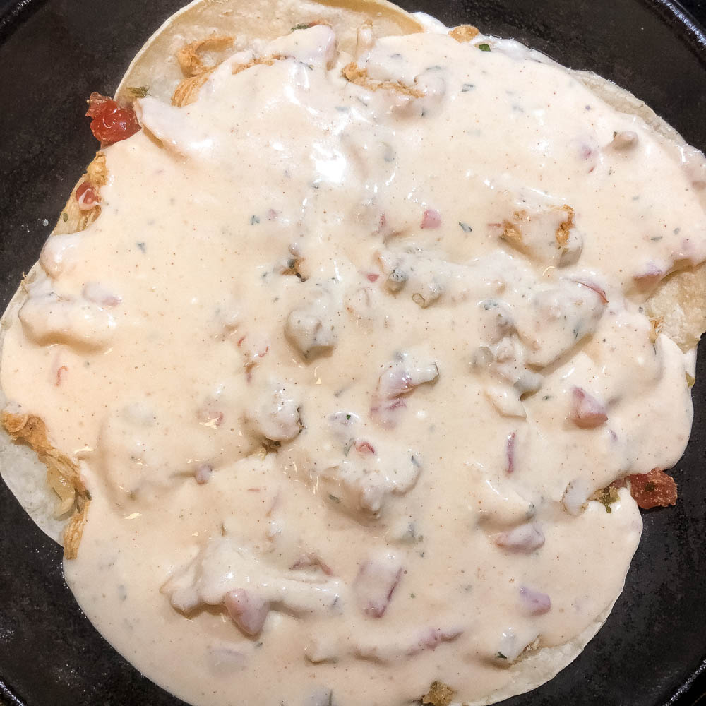 Sour cream enchilada sauce covering seasoned veggies and chicken and corn tortillas in a black cast iron skillet.   https://asprinklingofcayenne.com