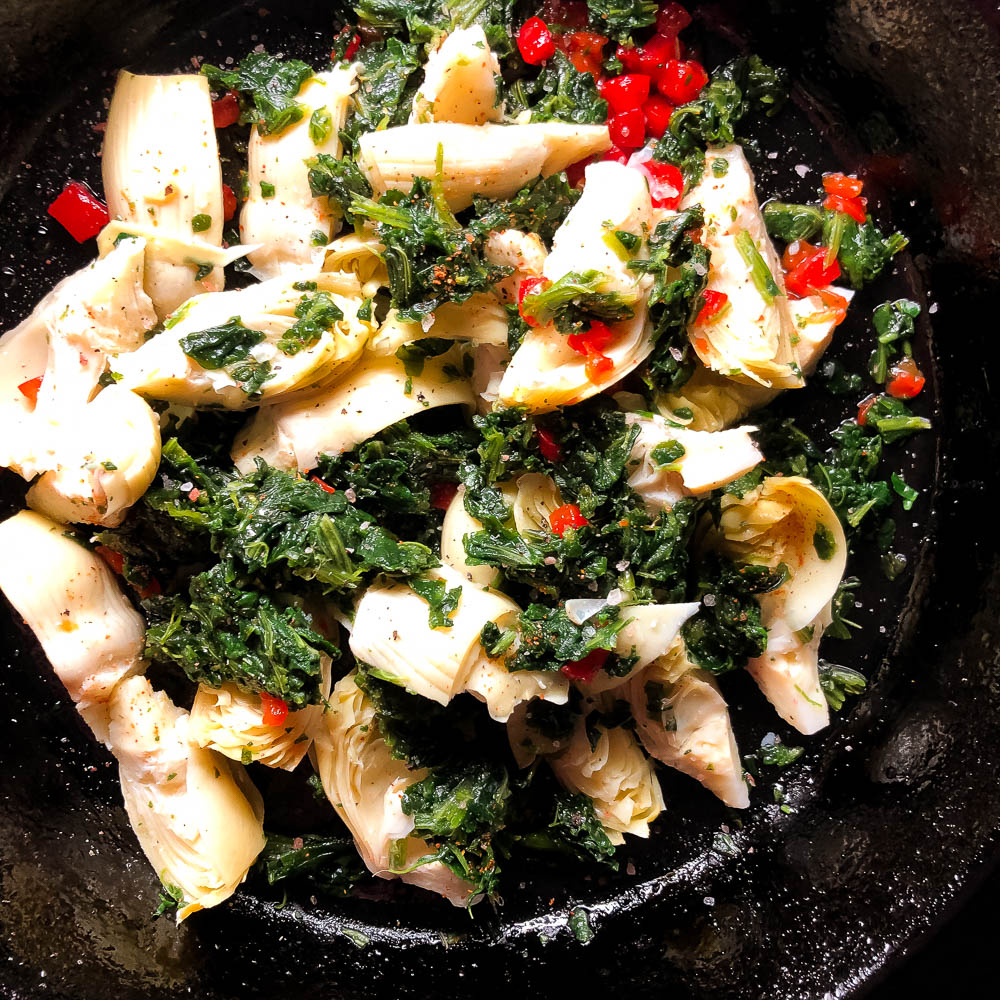 Artichoke hearts, thawed frozen spinach and pimentos in a cast iron skillet. | https://asprinklingofcayenne.com