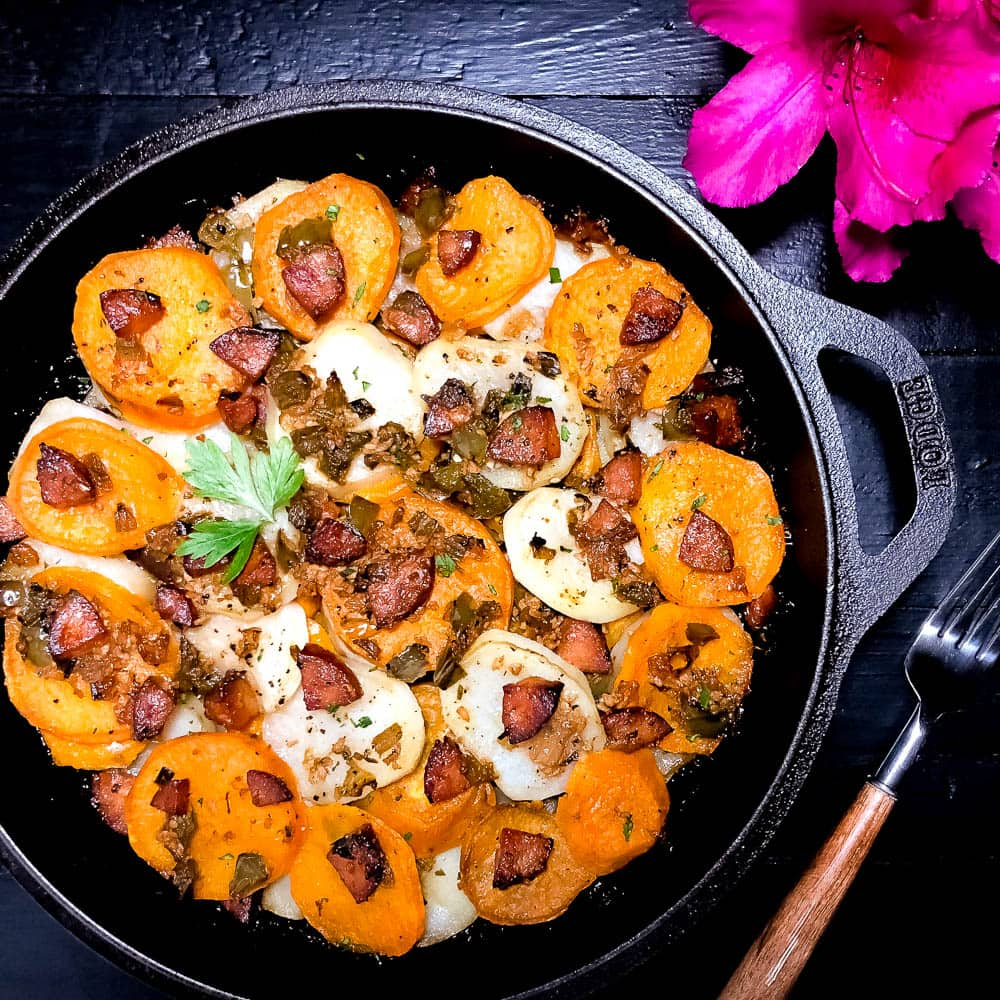 A black cast iron skillet holding freshly baked South Louisiana Sassified Skillet Potatoes with Sausage | https://asprinklingofcayenne.com