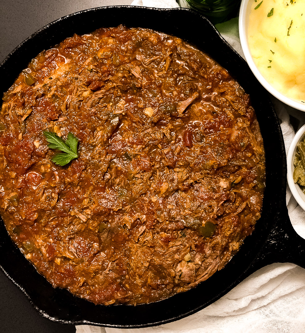 A black cast iron skillet filled with grain free Creole red gravy.