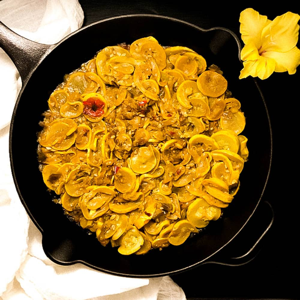 A black cast iron skillet filled with Cajun Smothered Yellow Squash