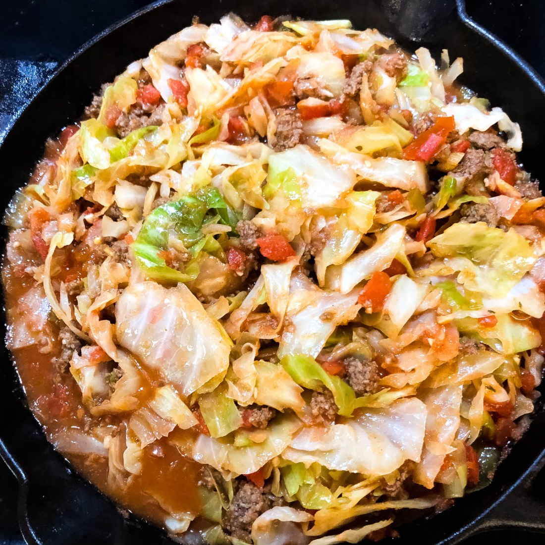 Red gravy, wilted cabbage, ground beef and the Cajun trinity in a black cast iron skillet.
