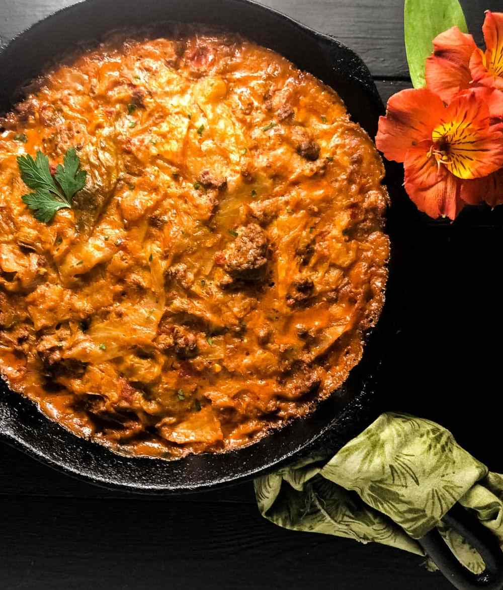 A black iron skillet filled with Keto Low Carb Cheesy Cajun Cabbage Casserole