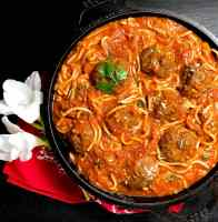 A black cast iron skillet filled with Gluten Free Creole Spaghetti and Meatballs