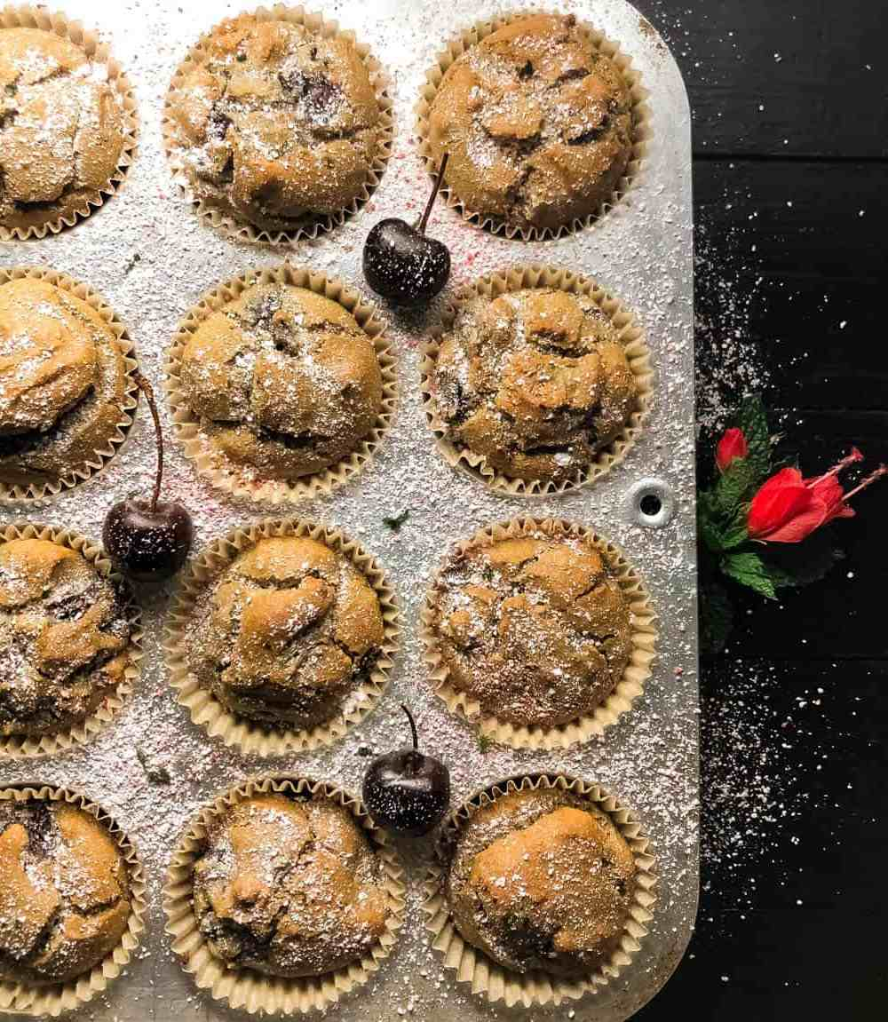 A silver muffin tin filled with Grain Free Cherry Muffins against a black background with a red flower.