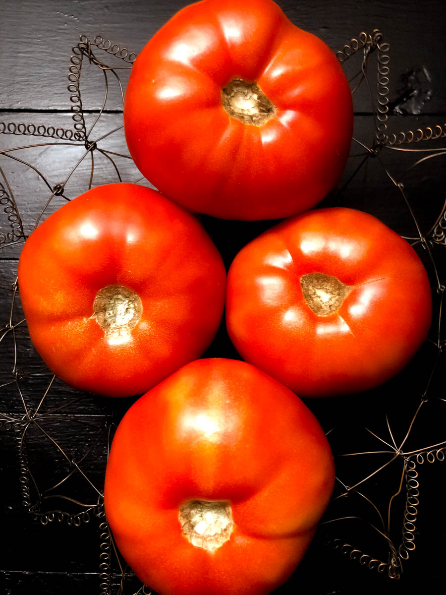 South Louisiana Creole tomatoes in a wire basket against a black background.