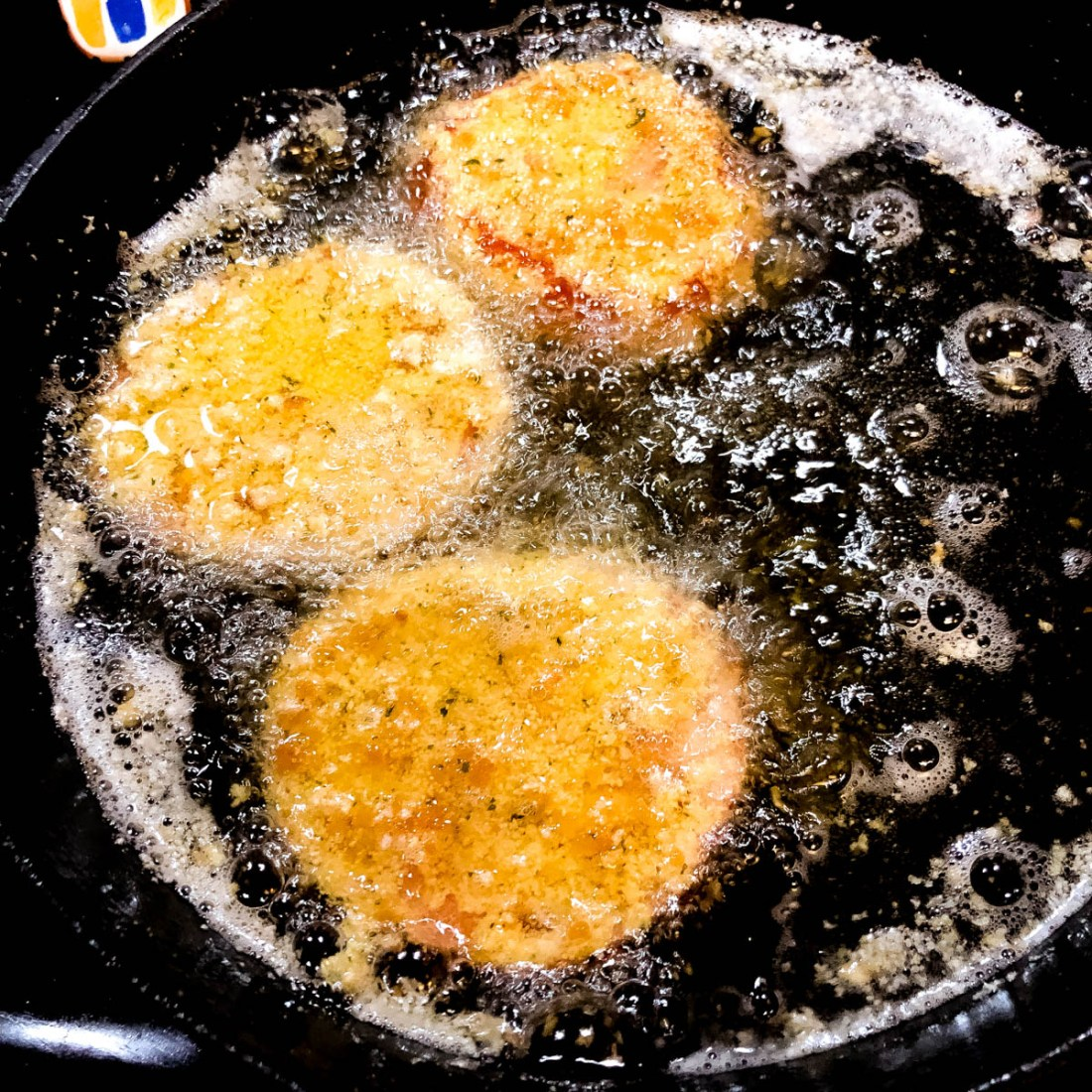 Gluten free battered red tomatoes frying in a cast iron skillet.