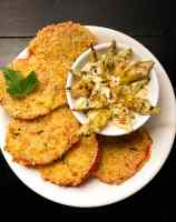 A round white plate filled with Gluten Free Fried Creole Tomatoes with Roasted Artichoke Remoulade against a black background.