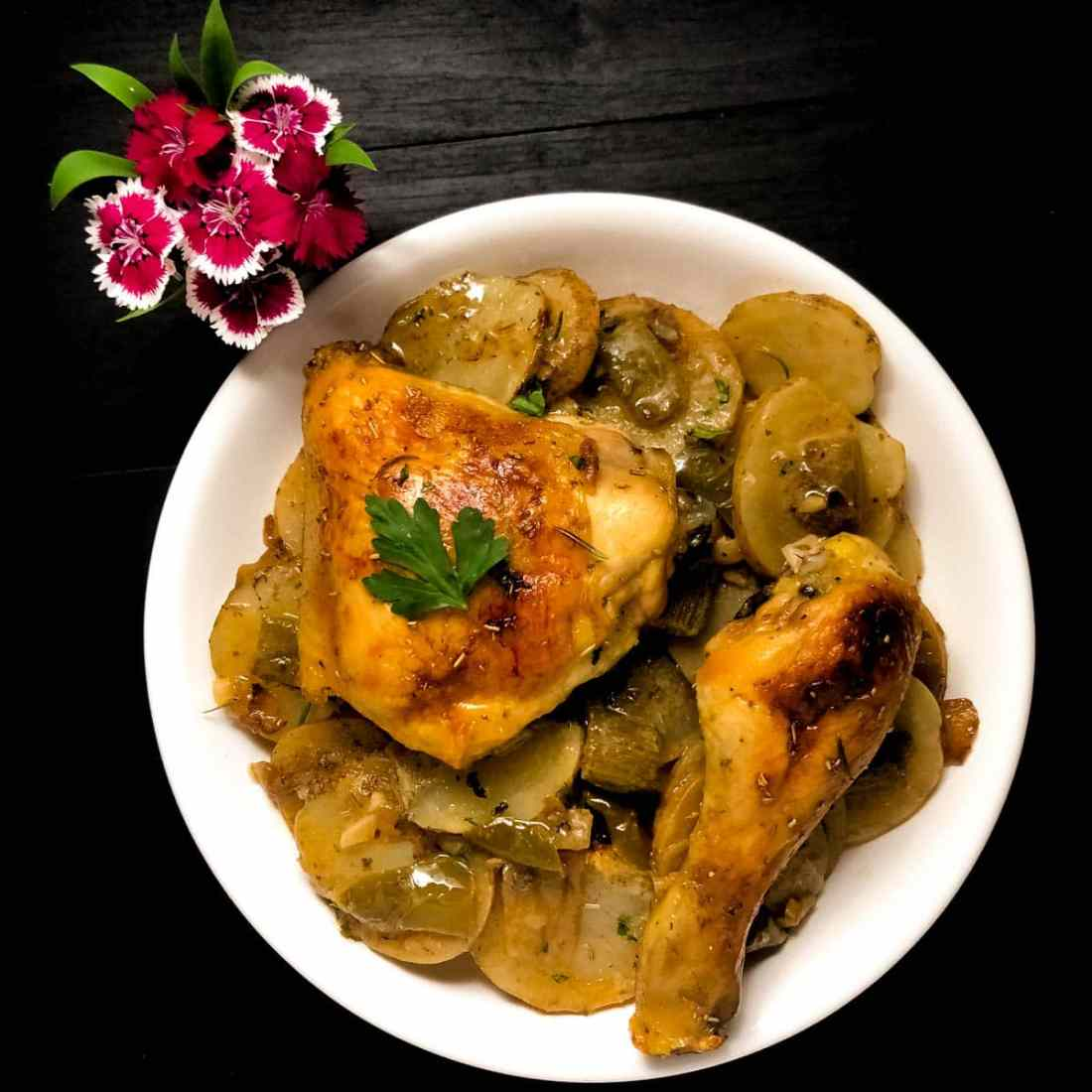 A white bowl filled with baked Cajun style rosemary lemon chicken and potatoes against a black background with hot pink flowers.