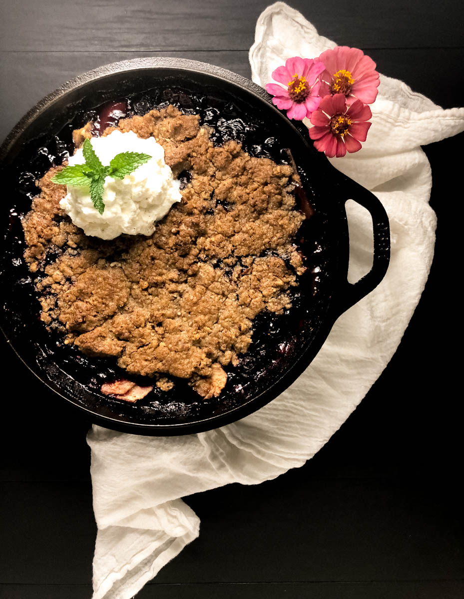 Freshly baked grain free blueberry pear crisp in a black iron skillet against a black background.