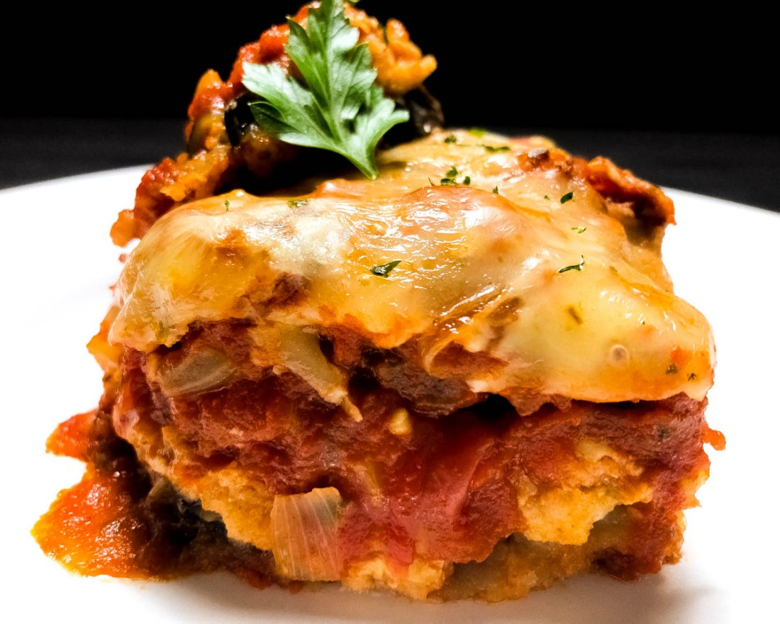 A close-up of Creole style gluten free eggplant Parmesan on a white plate against a black background.