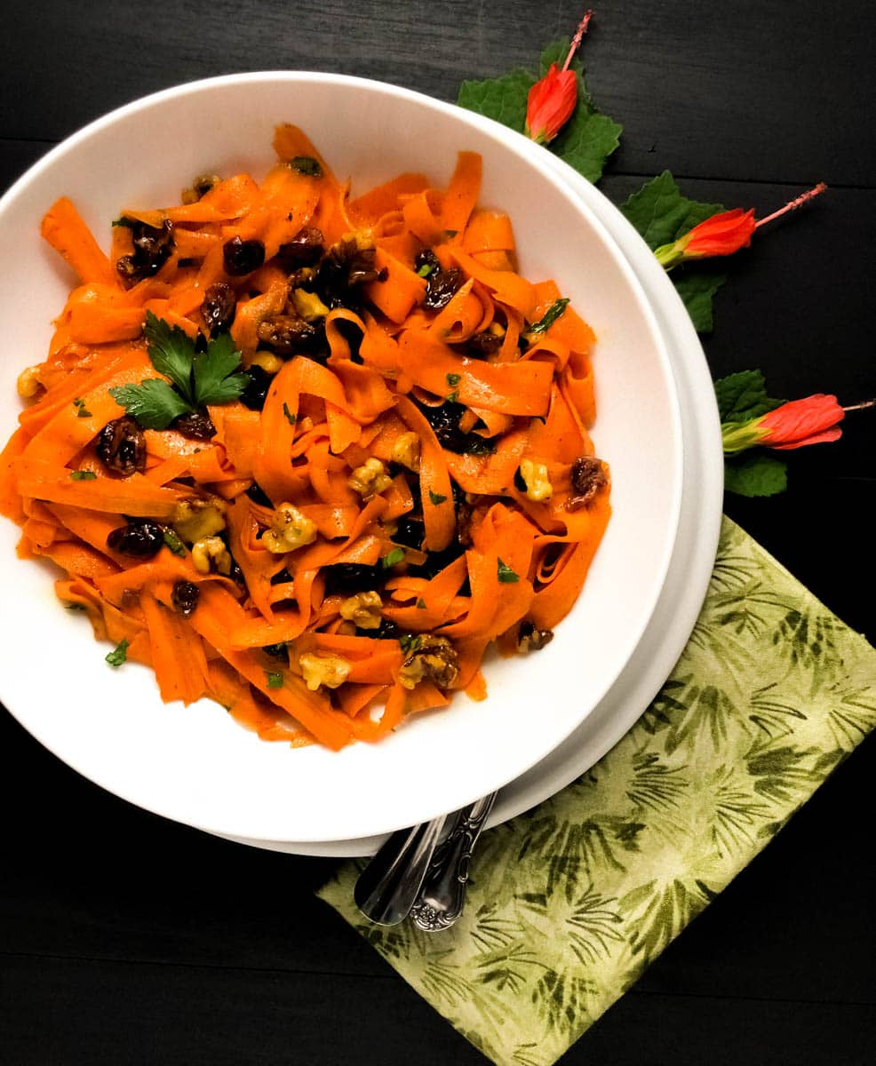 Candied Carrot Salad in a round white bowl with red flowers against a black background.