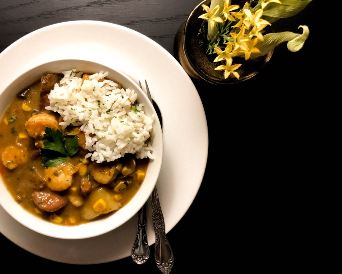 Shrimp, Corn Maque Choux and Sausage Stew in a round white bowl against a black background.