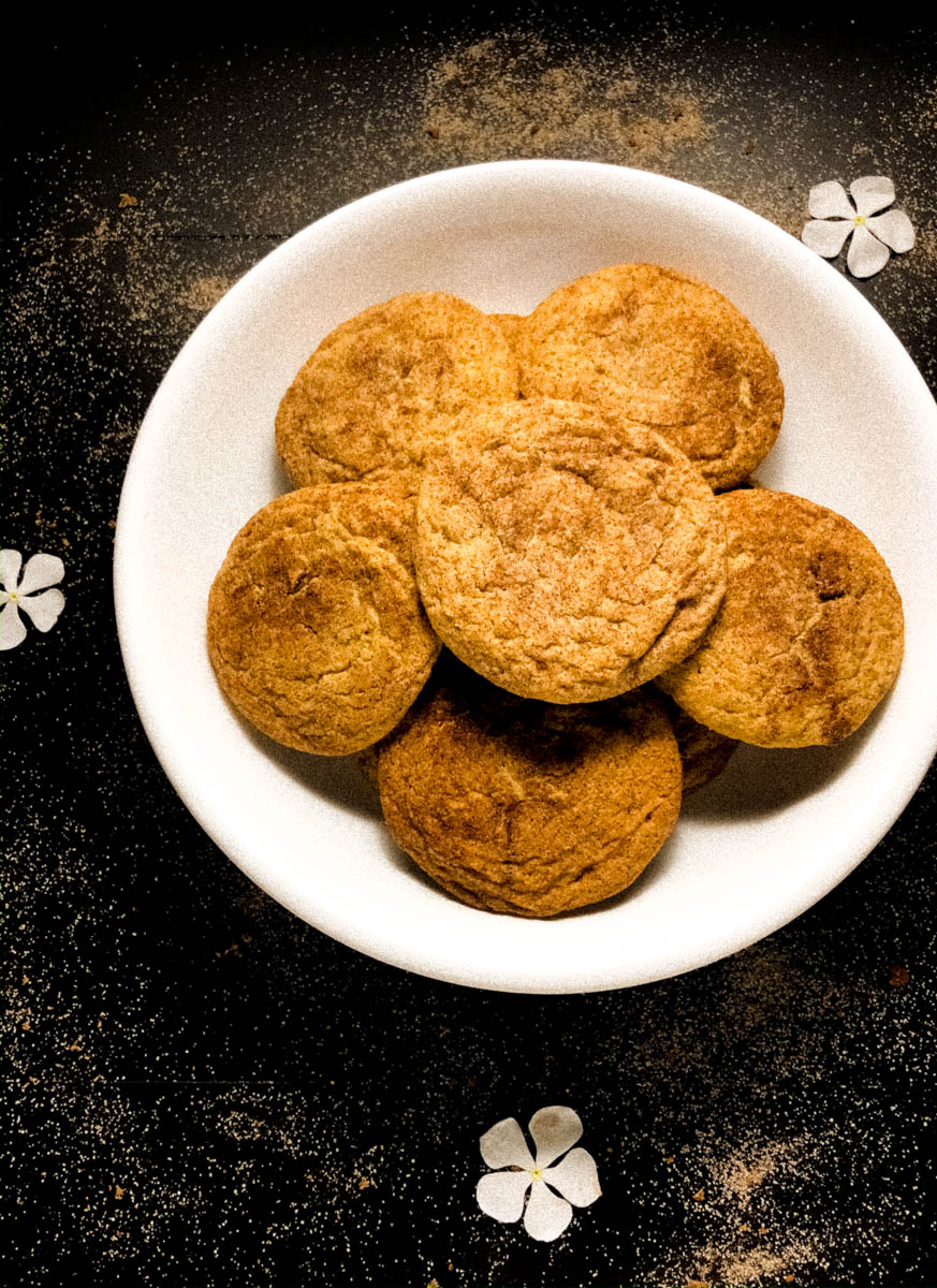 Gluten Free Snickerdoodles cookies in a white bowl against a black background.