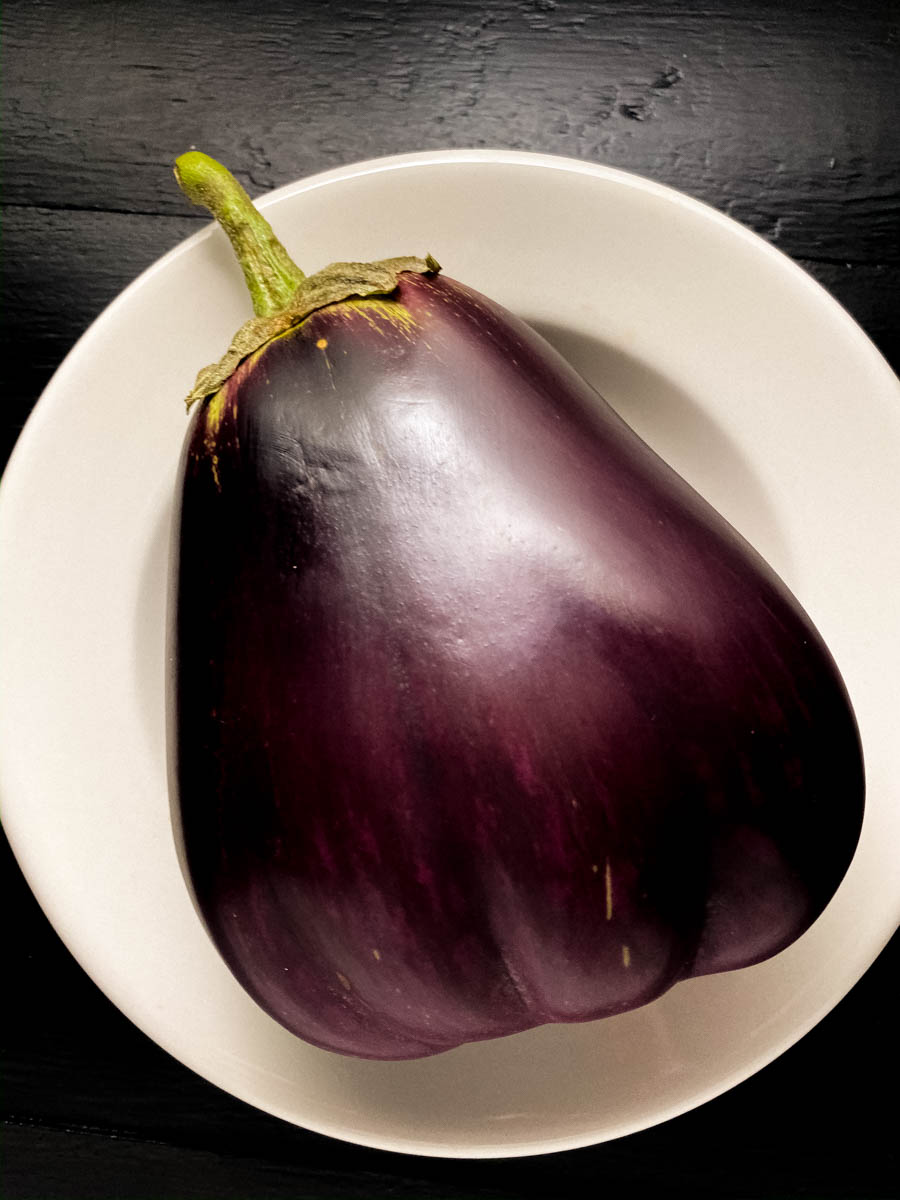 A garden grown raw eggplant against a white plate.