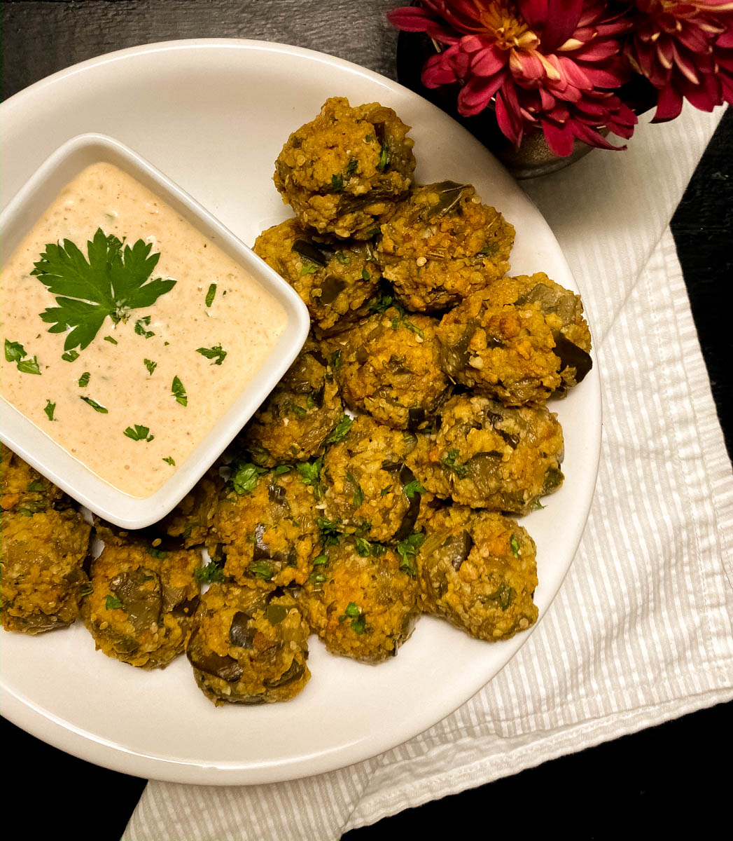 A white round plate filled with GF eggplant meatballs with Cajun remoulade sauce.