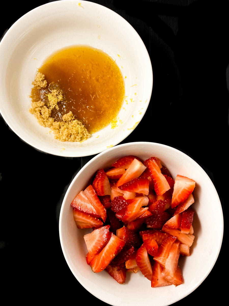 A bowl of strawberries and a bowl filled with lemon juice, maple syrup, lemon zest, and brown sugar.