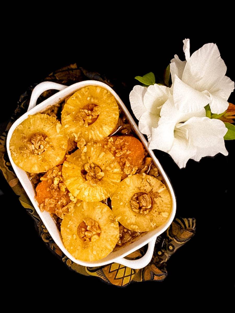 A white casserole dish filled with Walnut Sweet Potato Pineapple Breakfast Bake