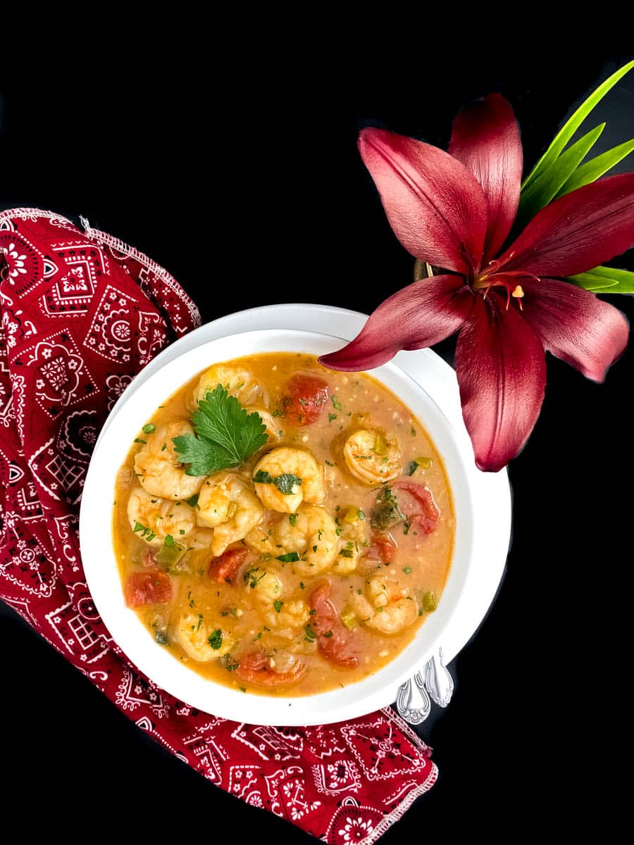 A round white bowl filled with keto Paleo gluten free Cajun shrimp etoufee against a black background.