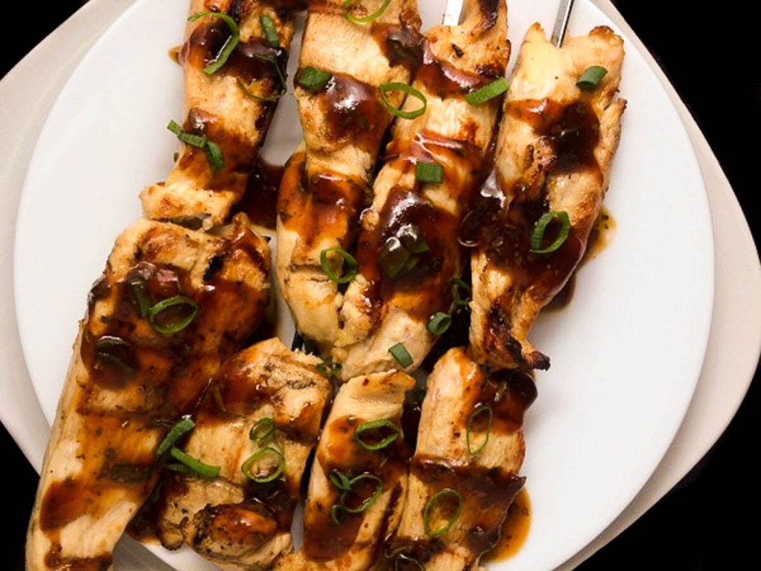 A white plate topped with Chicken Skewers with Asian Awesome Sauce.
