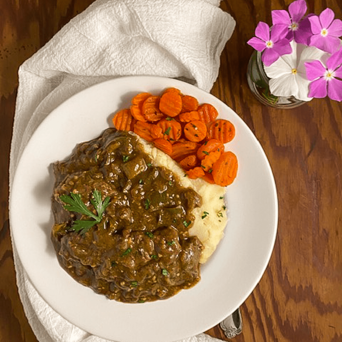 A round white plate filled with gluten free Cajun smothered steak and gravy, mashed potatoes and baked carrots.