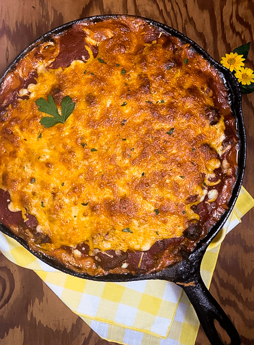 A cast iron skillet filled with Creole-Style Baked Million Dollar Spaghetti against a brown background.