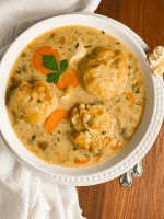 A round white bowl filled with Cajun-style gluten free chicken and dumplings.