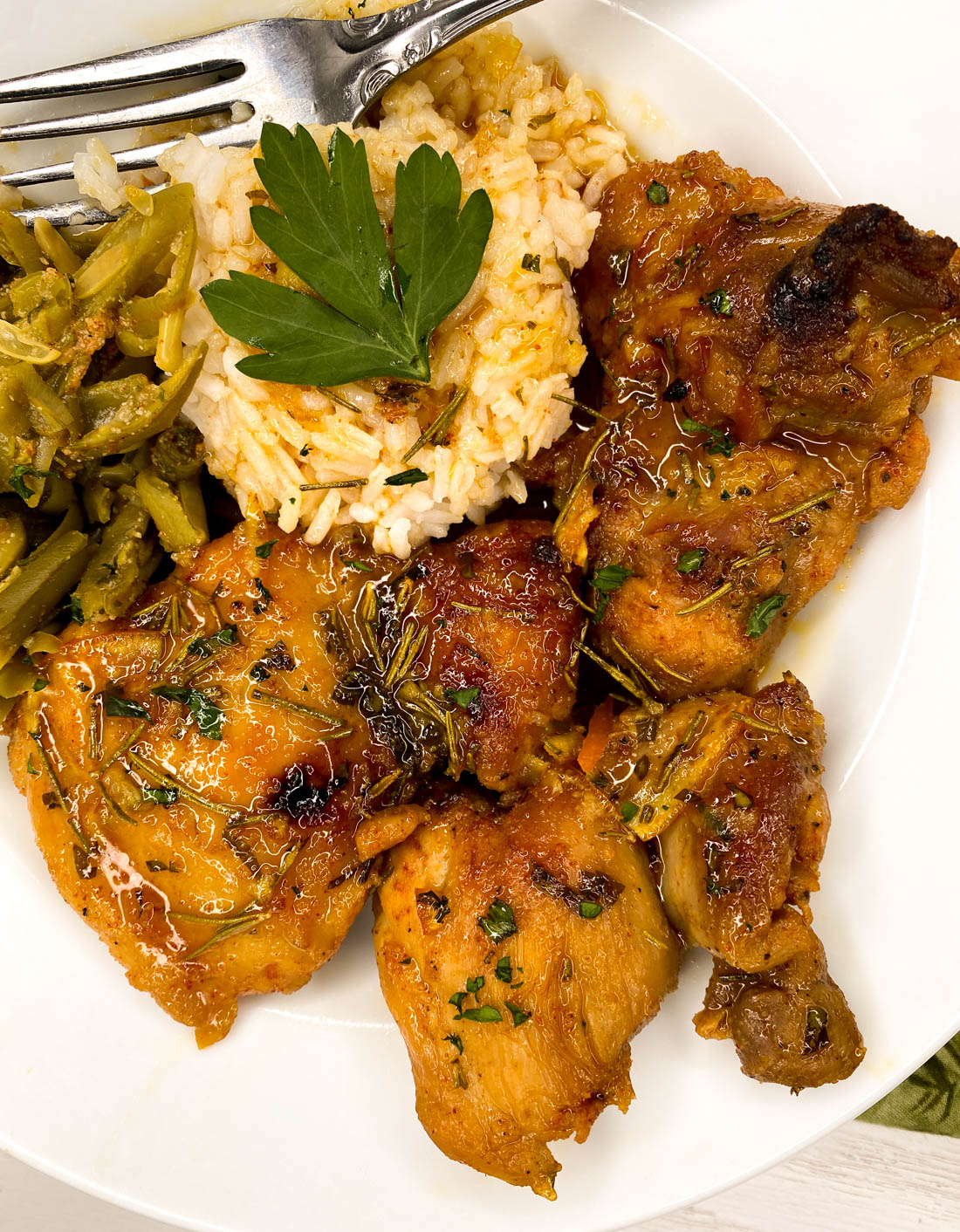 A white round plate filled with green beans, rice and cayenne rosemary orange marmalade chicken thighs {grain and gluten free}.
