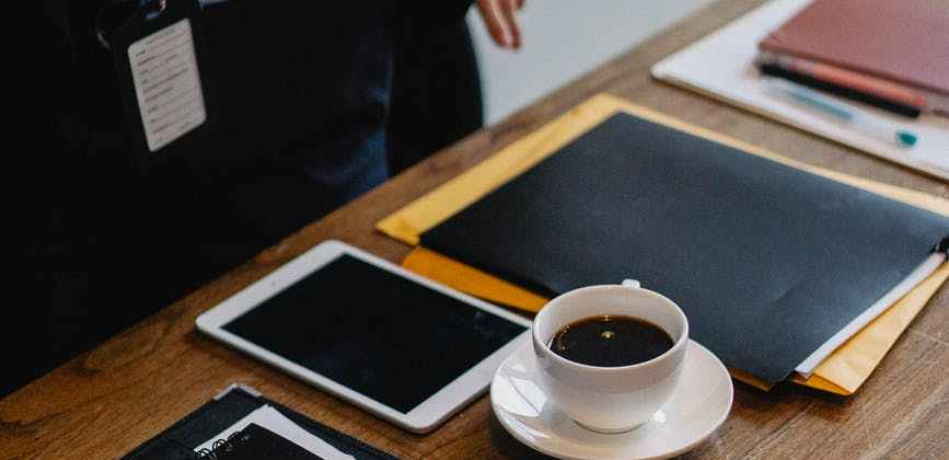 businessperson standing near table with cup of coffee and folders