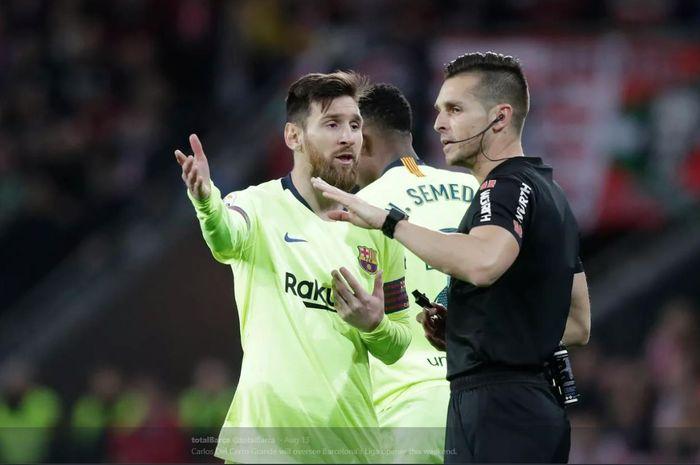 Wasit Carlos Del Cerro Grande (kanan) berbicara dengan Lionel Messi.